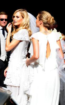 Poppy is helped by her sister Cara Delevingne (right) as she prepares to walk up the aisle. Photo: Ian West/PA Wire