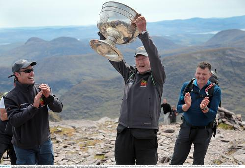 16 May 2014; Legendary GAA Commentator Mícheál Ó Muircheartaigh lifts the Sam Maguire Cup on the Summit of Carrauntoohil, MacGillycuddy's Reeks, Co. Kerry, with programme director and former Galway star Alan Kerins, left, and Tom Prendergast, 1969 Kerry All- Ireland winner, during the 'Sam to Summit' in aid of the Alan Kerins Project which saw Sam Maguire and representatives and players with All-Ireland football medals from each of the 32 counties reach the top of Irelands highest mountain. Carrauntoohil, Co. Kerry. Picture credit: Valerie O'Sullivan / SPORTSFILE