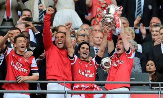 (L-R) Arsenal's Mesut Ozil, Lukas Podolski, Mikel Arteta and Thomas Vermaelen celebrate with the FA Cup trophy in the stands after during the FA Cup Final at Wembley Stadium, London. Nick Potts/PA Wire.