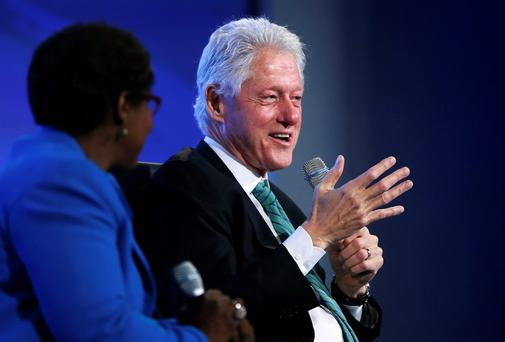 Former U.S. President Bill Clinton (R) smiles as he answers a question about recent remarks by Republicans about his wife Hillary Clinton's health