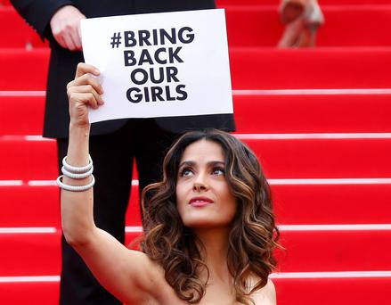 Actress and producer Salma Hayek holds a placard which reads