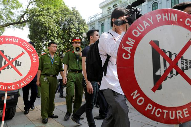 A Vietnamese police officer uses a speaker to order pedestrians including journalists to leave a closed area near the Chinese Embassy in Hanoi, Vietnam