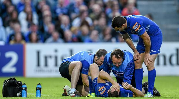 Dave Kearney, Leinster, is treated for an injury by team doctor Dr. John Ryan and physiotherapist Garreth Farrell, left, watched by his brother Rob, after picking up an injury in the second half. Picture credit: Ramsey Cardy / SPORTSFILE