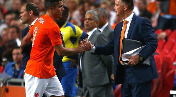 Robin van Persie is congratulated by his Dutch manager, Louis van Gaal, after he was substituted during the friendly against Ecuador in Amsterdam - the pair are set to link up at Manchester United after the summer