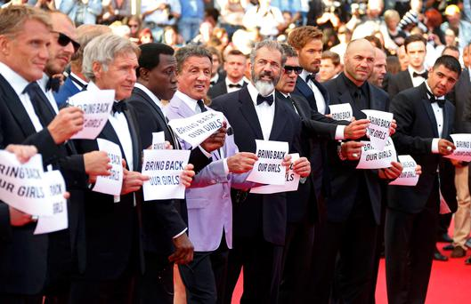 """Actors Sylvester Stallone (C) and cast members of the film """"The Expendables 3"""" hold placards which read """"Bring back our girls"""" as they pose on the red carpet during the 67th Cannes Film Festival in Cannes May 18, 2014. From L, Dolph Lundgren, Harrison Ford, Wesley Snipes, Sylvester Stallone, Mel Gibson, Antonio Banderas, Kellan Lutz, Jason Statham and Victor Ortiz. REUTERS/Yves Herman (FRANCE - Tags: ENTERTAINMENT TPX IMAGES OF THE DAY)"""