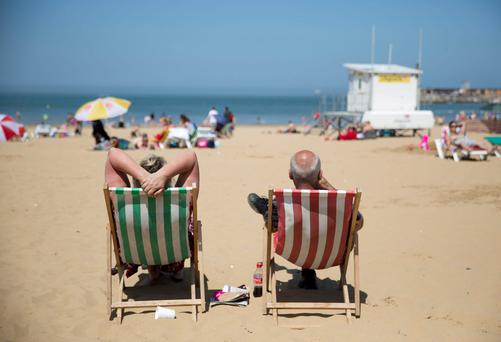 A couple sit on the beach in deckchairs in Margate, southern England May 18, 2014. Much of Britain enjoyed warm and sunny weather, on Sunday.