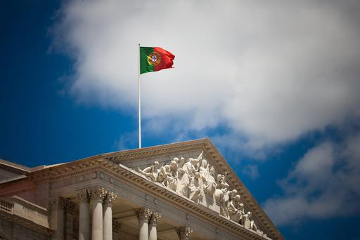 A Portuguese national flag flies above the parliament building in Lisbon