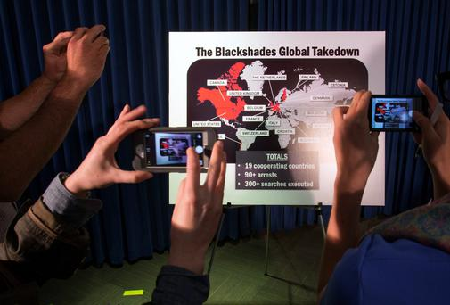 "Journalists take photographs of a display referring to ""BlackShades"" malware during a news conference by the U.S. Attorney for the Southern District of New York to announce law enforcement action. Photo: Reuters."