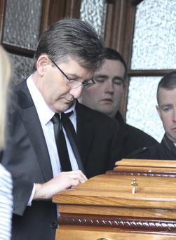 Daniel O'Donnell wipes the rain from the coffin of his late mum Julie as they enter the little chruch at Kincasslagh. Photo: Joe Boland