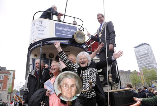 Agnes Malone (in check jacket), second cousin of trade unionist Rosie Hackett (inset), waves from a 1920s-era tram during the official naming of The Rosie Hackett Bridge