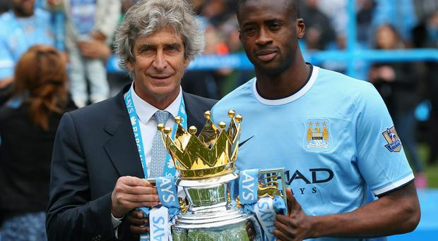 MANCHESTER, ENGLAND - MAY 11: The Manchester City Manager Manuel Pellegrini and Yaya Toure pose with the trophy at the end of the Barclays Premier League match between Manchester City and West Ham United at the Etihad Stadium on May 11, 2014 in Manchester, England. (Photo by Alex Livesey/Getty Images)