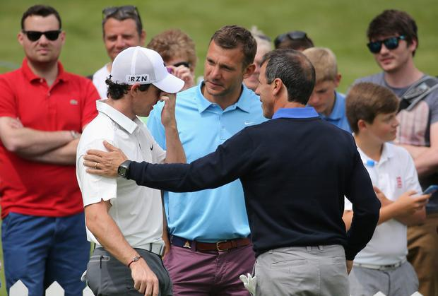 Rory McIlroy of Northern Ireland chats to former footballers Andriy Shevchenko and Gianfranco Zola (R) on the putting green