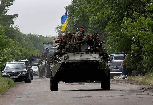 Ukrainian soldiers ride atop an Armoured Perssonel Carrier (APC) as they drive through the site where pro-Russian rebels killed thirteen Ukrainian servicemen on the outskirts of the eastern Ukrainian town of Volnovakha, south of Donetsk. Reuters