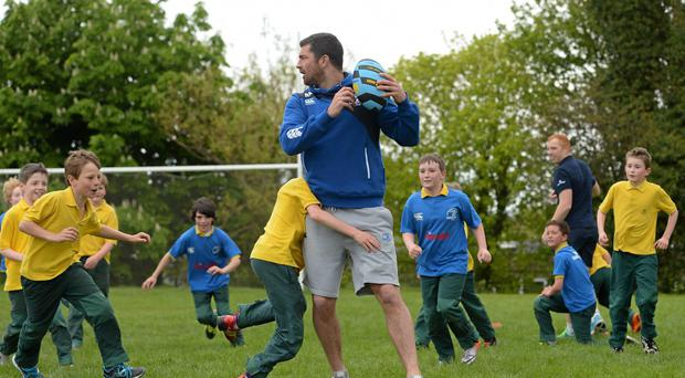 Leinster star Rob Kearney is tackled by St Patrick's Boys' National School pupil James Boland at the launch of Summer Camps. Photo: Stephen McCarthy / SPORTSFILE