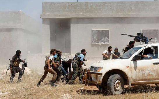 Free Syrian Army fighters help a fellow fighter wounded after what they said was clashes with forces loyal to Syria's President Bashar al-Assad, in the town of Morek in Hama province