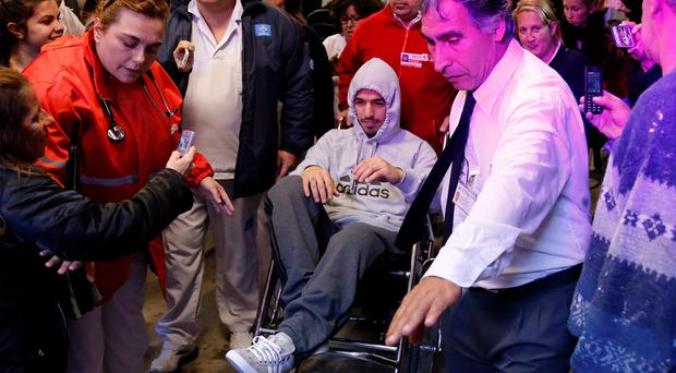 Uruguayan striker Luis Suarez leaves the hospital in a wheel chair after surgery due to a knee injury in Montevideo