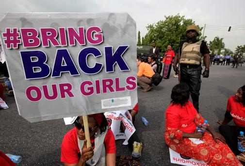 A police officer stands guard as people attend a demonstration calling on the government to rescue the kidnapped girls of the government secondary school in Chibok, in Abuja, Nigeria. Scores of protesters chanting