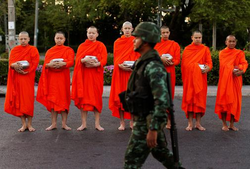 A soldier walks past Buddhist monks begging for alms outside a temple in Bangkok