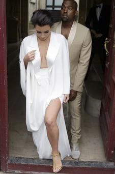 American reality TV star Kim Kardashian (L) and American singer Kanye West (R) leave their residence in Paris on May 23, 2014, ahead of their wedding