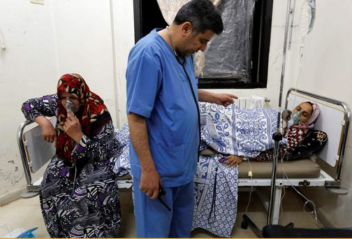 Women, affected by what activists say was a gas attack, receive treatment inside a makeshift hospital in Kfar Zeita village in the central province of Hama