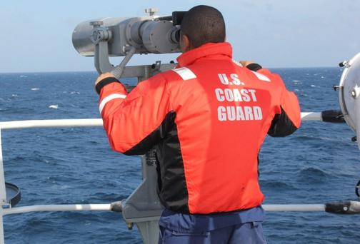 A crew member of the U.S. Coast Guard Cutter Vigorous searches for crew members of the sailing vessel Cheeki Rafiki, about 1,000 miles off Cape Cod