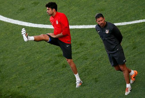 Atletico Madrid coach Diego Simeone in pensive mood as Diego Costa does some stretching in Lisbon