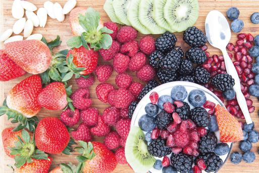 Preparing a delicious healthy berry fruit salad with assorted fresh fruit on the counter including strawberries, raspberries, blackberries, blueberries, pomegranate and kiwifruit with almonds