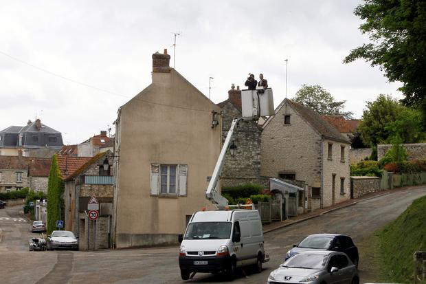 A videoman uses a crane to film the arrival of Kim Kardashian, Kanye West and their guests in the street facing the entrance of the Wideville Castle, in Davron, 35 miles west of Paris, Friday, May 23, 2014. The gates of the Chateau de Versailles, once the digs of Louis XIV, will be thrown open to Kim Kardashian, Kanye West and their guests for a private evening on the eve of their marriage. (AP Photo/Francois Mori)