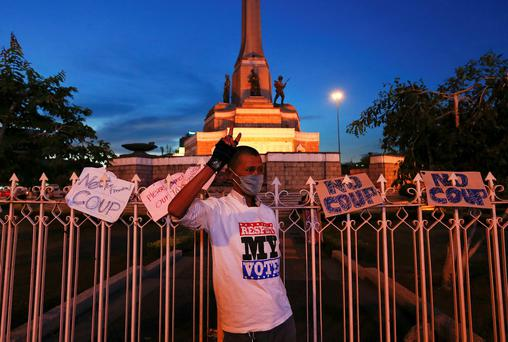 A protester poses for a photo next to signs left at the fence, by those protesting against military rule, around the Victory Monument in Bangkok. Former Thai Prime Minister Yingluck Shinawatra was in a