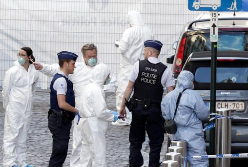 Forensic experts examine the site of a shooting at the Jewish museum in Brussels. Belgian officials say that at least three people have been killed in gunfire at the Jewish Museum in Brussels.