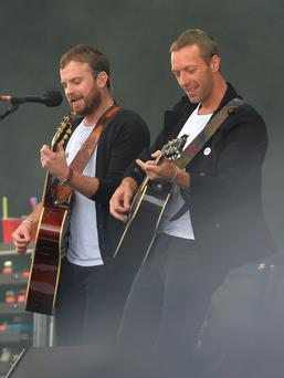The Kings of Leon with Chris Martin (right) of Coldplay performing during Radio 1's Big Weekend at Glasgow Green, Glasgow. Mark Runnacles/PA Wire