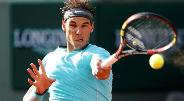 Rafael Nadal returns the ball to Robby Ginepri during their men's singles match at the French Open tennis tournament at the Roland Garros stadium in Paris