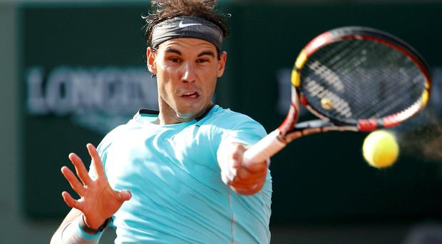 Rafael Nadal returns the ball to Robby Ginepri during their men's singles match at the French Open at Roland Garros