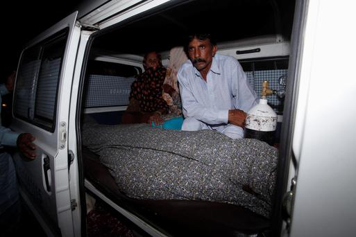 Mohammad Iqbal sits next to his wife Farzana's body, who was killed by family members, in an ambulance outside of a morgue in Lahore. Reuters/Mohsin Raza
