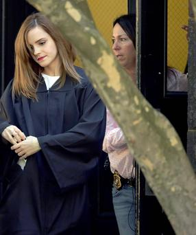 Actress Emma Watson, left, is accompanied by a woman wearing a badge and with the handle of a handgun visible at her side, as she walks on campus following commencement services at Brown University in Providence, R.I. AP