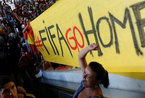 A demonstrator shout slogans against FIFA during a protest against FIFA World Cup, at a bus station in Brasilia, Brazil