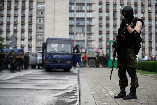 An armed pro-Russian separatist stands guard on a street outside the regional administration building in the east Ukrainian city of Donetsk