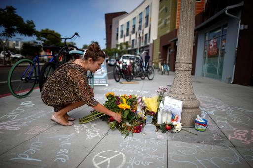 A student leaves flowers at a tribute for victims