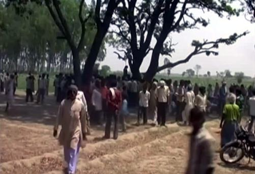 A crowd gathers near where two teenage sisters were found hanging from a mango tree in Katra village in Uttar Pradesh state, in northern India. The crowd refuses to allow police take down the bodies in protest at their alleged inaction in the case
