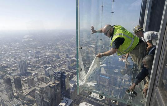 Glaziers from MTH Industries finish replacing a layer of protective coating over the glass surface on the floor of one of four transparent ledges that jut out from the 103rd floor of the Willis Tower in Chicago. (AP Photo/M. Spencer Green)