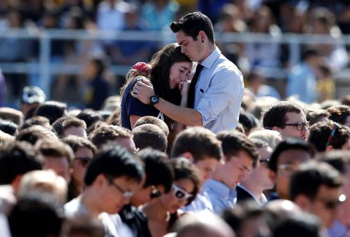 A couple embrace before a memorial service at Harder Stadium on the campus of the University of California, for the victims of the rampage by Elliot Rodger which left six people dead