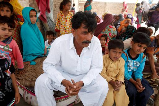 Muhammed Iqbal, 45, husband of the late Farzana Iqbal, sits with his family members at his residence in a village in Moza Sial, west of Lahore