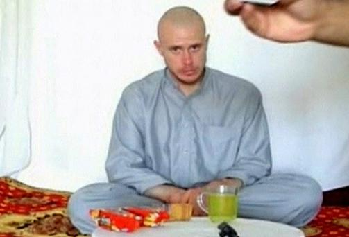 U.S. Private Bowe Bergdahl watches as one of his captors displays his identity tag to the camera at an unknown location in Afghanistan