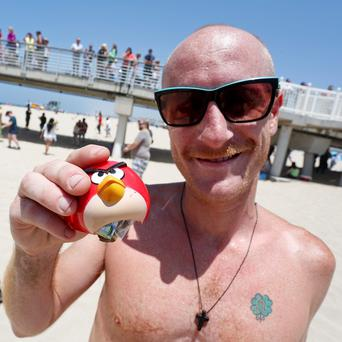 Brian Fitzpatrick holds a plastic Angry Bird orb filled with cash that he found in Hermosa Beach, California. Reuters/Jonathan Alcorn