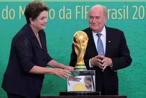FIFA president Sepp Blatter and Brazil's president Dilma Rousseff with the World Cup trophy during a ceremony in Brasilia yesterday. Reuters