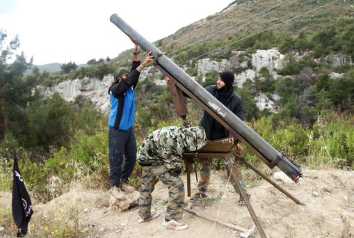 Rebel fighters prepare to fire a Grad rocket towards forces loyal to Syria's President Bashar al-Assad stationed at the entrance of the coastal city of Lataqia, during what the rebels said was an attempt to disrupt the country's presidential elections June 3, 2014. Reuters/Alaa Khweled