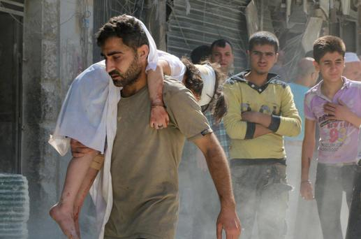 A man holds an injured child at a site hit by what activists said were barrel bombs dropped by forces loyal to Syria's President Bashar al-Assad in the al-Kalaseh neighbourhood in Aleppo. Reuters