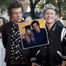 "Members of boy band One Direction, (L-R) Harry Styles, Niall Horan and Louis Tomlinson, pose for photographers at the world premiere of their film ""One Direction: This is Us"", in London August 20, 2013. REUTERS/Neil Hall (BRITAIN - Tags: ENTERTAINMENT SOCIETY) - RTX12RON"