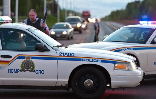 Royal Canadian Mounted Police officers use their vehicles to create a keep a perimeter in Moncton, New Brunswick on Wednesday June 4, 2014. The RCMP in New Brunswick said an undisclosed number of people have been shot and a manhunt is underway in the north end of Moncton for a man armed with guns.(AP Photo/The Canadian Press, Marc Grandmaison)