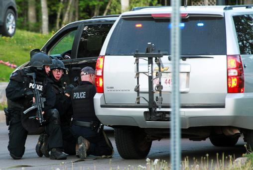 Emergency Response team members take cover behind vehicles in Moncton, New Brunswick June 4, 2014. Three police officers were shot dead and two more were wounded, police said as they conducted a manhunt for a man carrying a rifle and wearing camouflage clothes. Police said they were searching for Justin Bourque, 24, of Moncton. REUTERS/Ron Ward/Moncton Times & Transcript